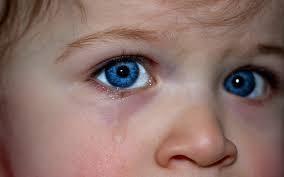 jong kind met blauwe ogen die bang en verdrietig lijken